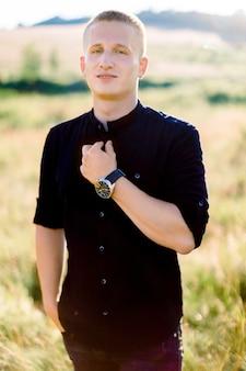 Porträt des hübschen blonden jungen kaukasischen mannes im schwarzen hemd und in den hosen, die im freien im schönen sommerfeld bei sonnenuntergang aufwerfen