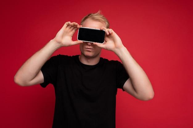 Porträt des hübschen blonden jungen mannes, der das stehende schwarze t-shirt trägt