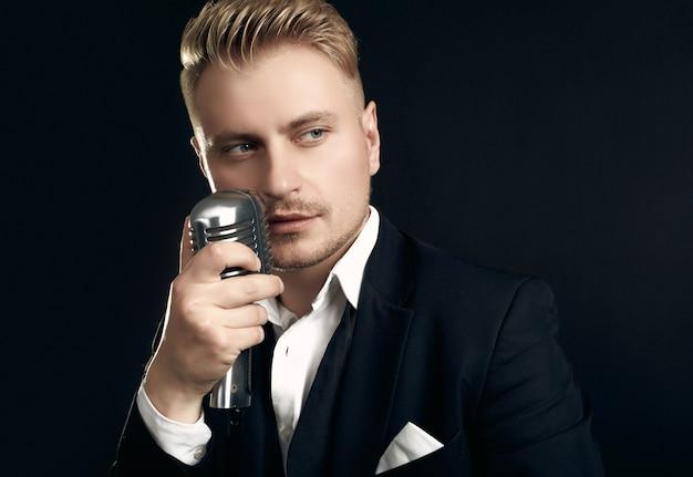 Porträt des hübschen blonden mannesängers im eleganten smoking und in der fliege, die mit weinlesemikrofon auf schwarzer wand aufwirft