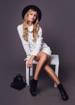 Porträt des hübschen blonden modells, das auf dem tisch im weißen lässigen warmen strickpullover und im schwarzen hut sitzt