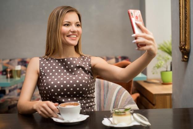 Porträt des hübschen braunhaarigen mädchens, das selfie auf ihrem handy am restauranttisch macht