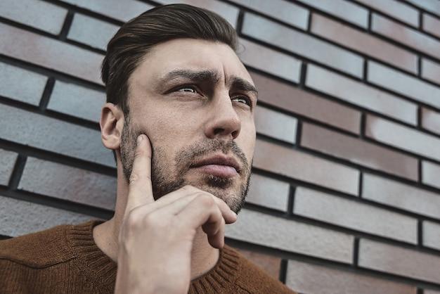 Porträt des hübschen ernsten mannes, der an etwas lokalisiert auf brauner backsteinmauer denkt.