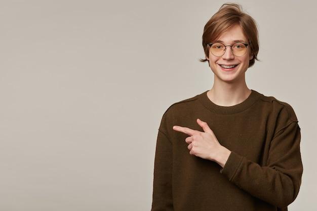 Porträt des hübschen, erwachsenen mannes mit blonden haaren. tragen eines braunen pullovers und einer brille. hat zahnspangen.