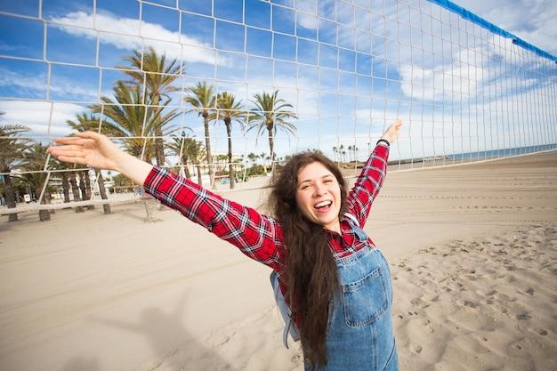 Porträt des hübschen frauentouristen, der am heißen strand nahe volleyballnetz während des heißen sommers steht