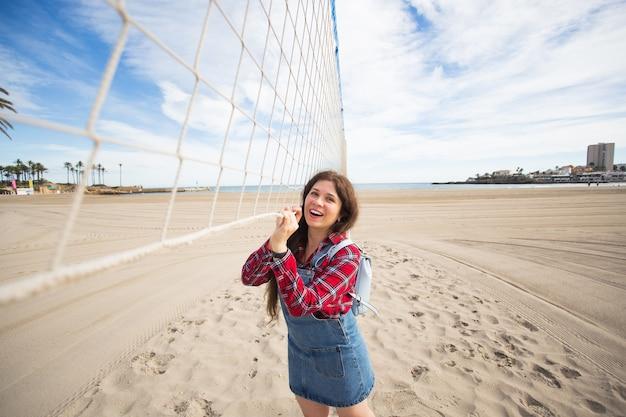 Porträt des hübschen frauentouristen, der auf sandstrand nahe volleyballnetz während des heißen sommers steht