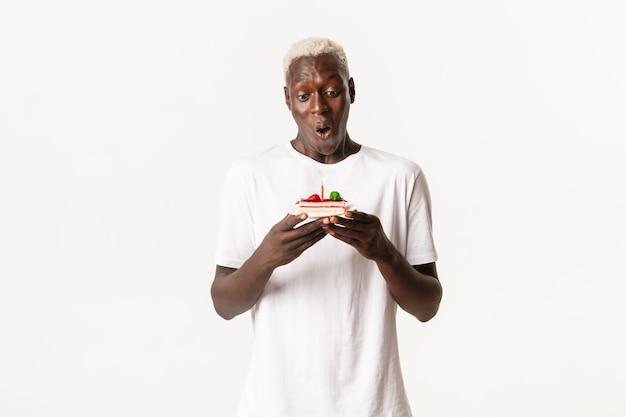 Porträt des hübschen, fröhlichen afroamerikanischen blonden mannes, der amüsiert auf ein stück geburtstagstorte schaut, wunsch macht und b-tag feiert