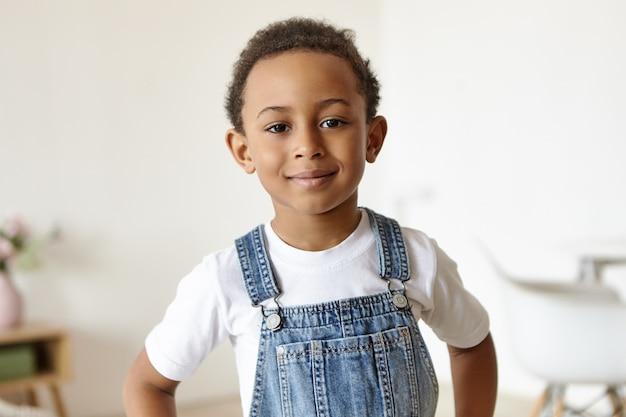 Porträt des hübschen fröhlichen kleinen jungen afrikanischen ursprungs, der drinnen aufwirft