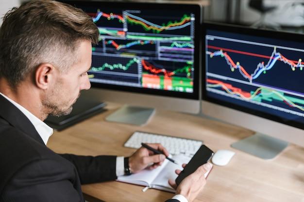 Porträt des hübschen geschäftsmanns 30s, der anzug unter verwendung des mobiltelefons beim arbeiten mit digitaler grafik auf computer im büro trägt