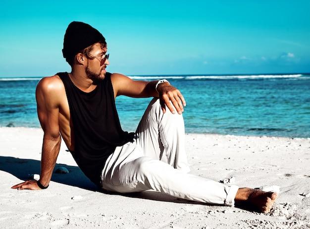 Porträt des hübschen hippies nahm das modemannmodell ein sonnenbad, das zufällige kleidung im schwarzen t-shirt und in sonnenbrille trägt, die auf weißem sand nahe blauem ozean und himmel sitzen