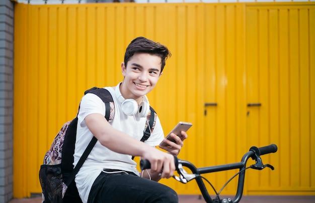 Porträt des hübschen jugendlich lächelnden, wenn er sein handy benutzt
