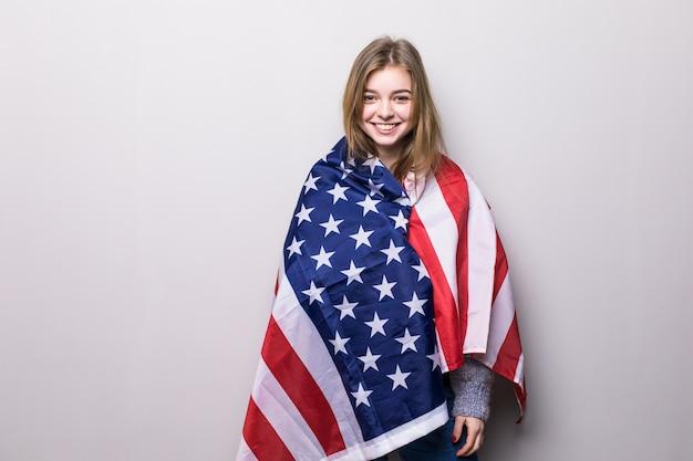 Porträt des hübschen jugendlich mädchens, das usa-flagge lokalisiert auf grau hält. 4. juli feier.