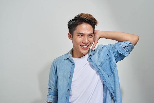 Porträt des hübschen jungen asiatischen kerls, der im studio aufwirft.