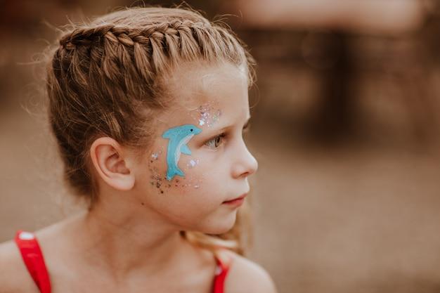 Porträt des hübschen jungen blonden mädchens an weißen flecken mit gesichtsbemalung des blauen delphins