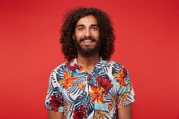 Porträt des hübschen jungen brünetten mannes mit üppigem bart und lockigem haar, das freudig mit breitem lächeln schaut, gekleidet in hemd mit blumendruck