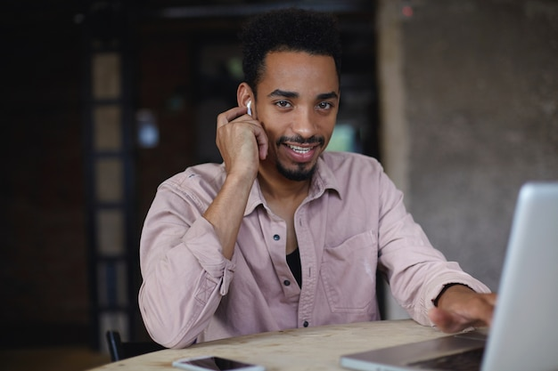 Porträt des hübschen jungen dunkelhäutigen männlichen freiberuflers mit bart, der außerhalb des büros im coworking space arbeitet, kopfhörer trägt und mit charmantem lächeln schaut