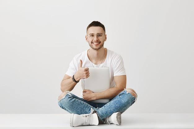 Porträt des hübschen jungen kerls mit brille, die mit seinem laptop aufwirft