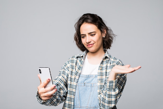 Porträt des hübschen jungen mädchens, das selbstporträt auf smartphone, mit offener handfläche schießt