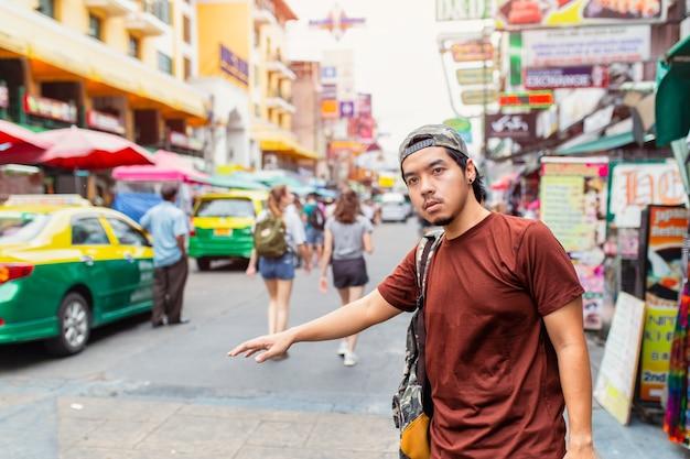 Porträt des hübschen jungen mannes, der auf der stadtstraße a steht
