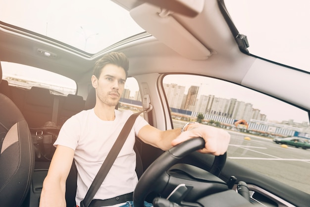 Porträt des hübschen jungen mannes, der ein auto fährt