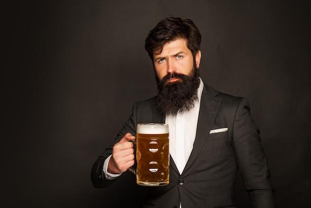 Porträt des hübschen jungen mannes, der ein gezapftes bier schmeckt. mann hält glas bier. hübscher bärtiger mann