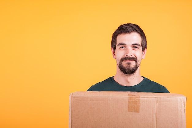 Porträt des hübschen jungen mannes, der eine kiste in seinen händen hält. lieferbote auf gelbem hintergrund