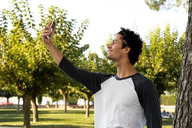 Porträt des hübschen jungen mannes, der sein handy draußen benutzt