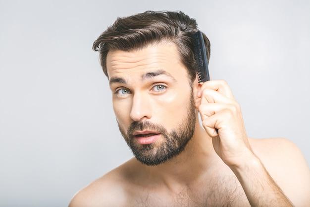Porträt des hübschen jungen mannes, der seine haare im badezimmer kämmt. isoliert über grauem hintergrund. Premium Fotos