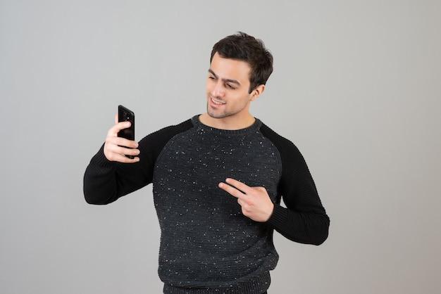 Porträt des hübschen jungen mannes, der über grauer wand steht und selfie nimmt