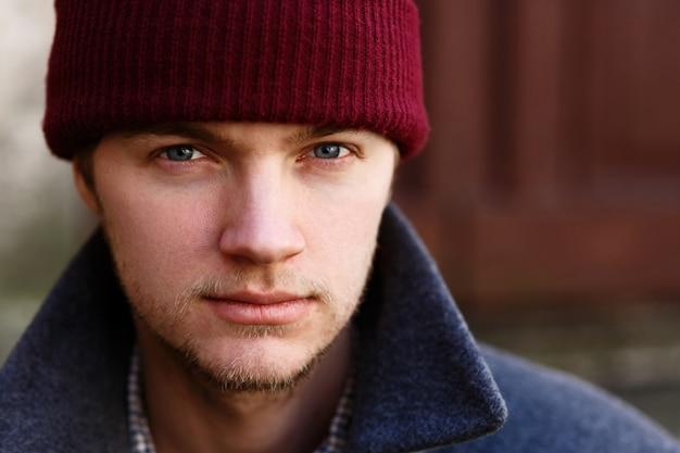 Porträt des hübschen jungen mannes im roten hut, der draußen aufwirft