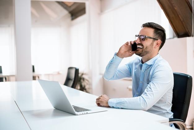 Porträt des hübschen jungen mannes in den gläsern, die am schreibtisch mit laptop-computer sitzen und am handy sprechen.