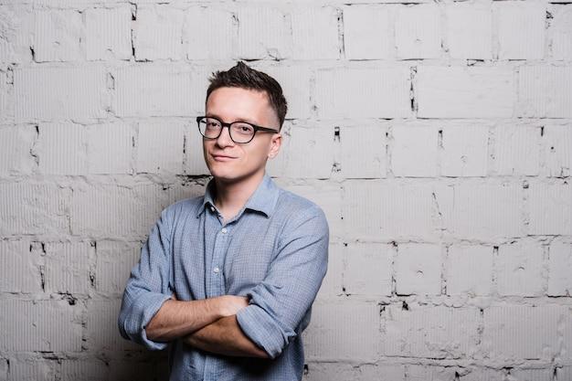 Porträt des hübschen jungen mannes in den jeanskleidern und in den brillen, die gegen graue ziegelwand stehen