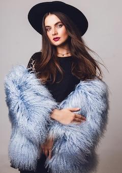 Porträt des hübschen jungen modells im stilvollen flauschigen wintermantel und im aufstellen des schwarzen hutes