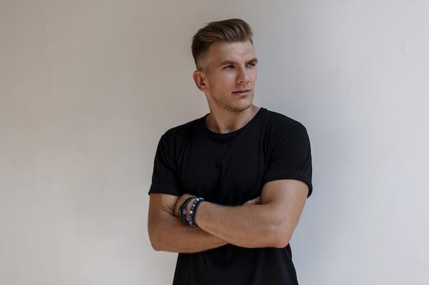 Porträt des hübschen jungen stilvollen mannmodells mit frisur im schwarzen mode-t-shirt steht nahe der wand