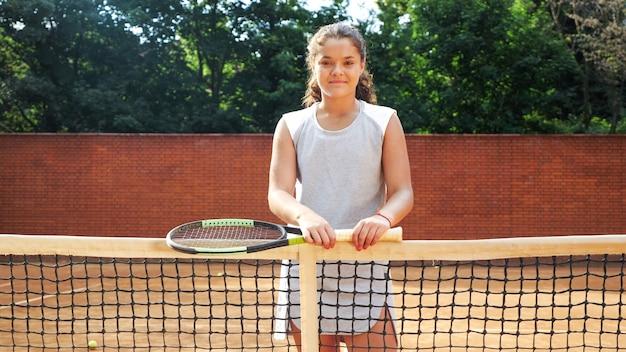 Porträt des hübschen jungen tennisspielmädchens, das mit schläger nahe netz auf orangefarbenem sandtennisplatz steht