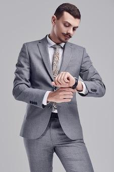 Porträt des hübschen jungen überzeugten arabischen geschäftsmannes mit grauem vollem anzug des fantastischen schnurrbartes in mode betrachtet seine uhr auf studiohintergrund