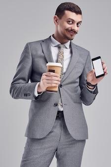 Porträt des hübschen jungen überzeugten arabischen geschäftsmannes mit grauem vollem anzug des fantastischen schnurrbartes in mode hält einen tasse kaffee und ein telefon auf studio