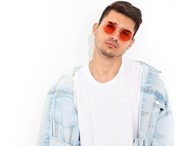 Porträt des hübschen jungen vorbildlichen mannes kleidete in der jeanskleidung bei der sonnenbrilleaufstellung an. isoliert