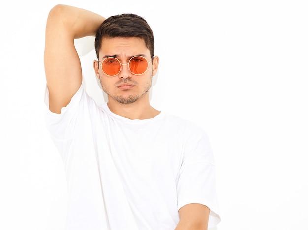 Porträt des hübschen jungen vorbildlichen mannes kleidete in der jeanskleidung und im t-shirt bei der sonnenbrilleaufstellung an. berührt seinen kopf