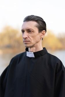 Porträt des hübschen katholischen priesters oder des pastors mit kragen