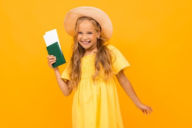 Porträt des hübschen kaukasischen mädchens mit langen kastanienbraunen haaren und hübschem gesicht im kleid hält einen pass und tickets