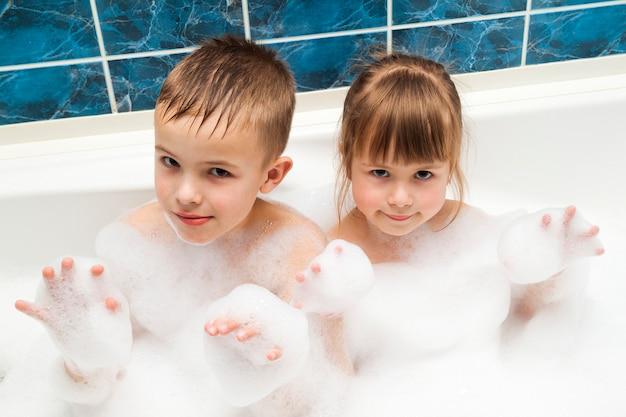 Porträt des hübschen kinderkleinen mädchens und -jungen im bad. hygienekonzept.