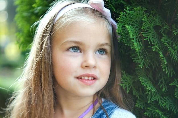 Porträt des hübschen kindermädchens, das draußen im sommerpark steht und glücklich lächelt.