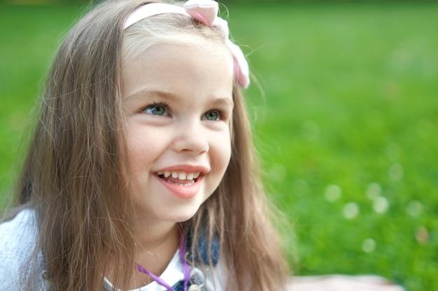 Porträt des hübschen kindermädchens im sommerpark, der glücklich lächelt.