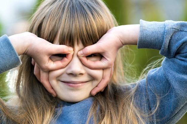 Porträt des hübschen kindermädchens mit grauen augen und langen blonden haaren, die draußen lächeln