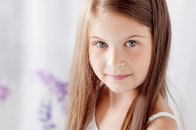 Porträt des hübschen kleinen gefühlsmädchens unter den violetten blumen. verschönern sie das bild des schönen lächelnden mädchens