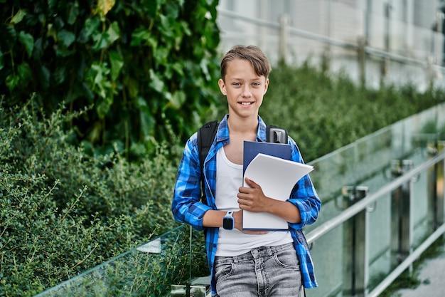 Porträt des hübschen kleinen glücklichen jungen des schülers mit rucksackbüchern und intelligenter uhr