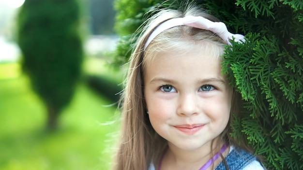 Porträt des hübschen kleinen kindermädchens, das draußen im sommerpark steht und glücklich lächelt.