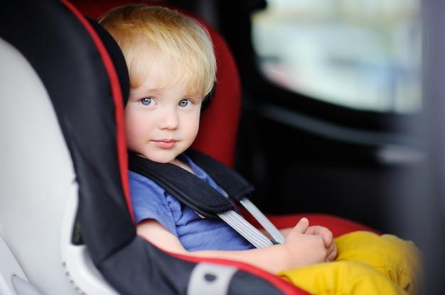 Porträt des hübschen kleinkindjungen sitzend im autositz. sicherheit beim transport von kindern
