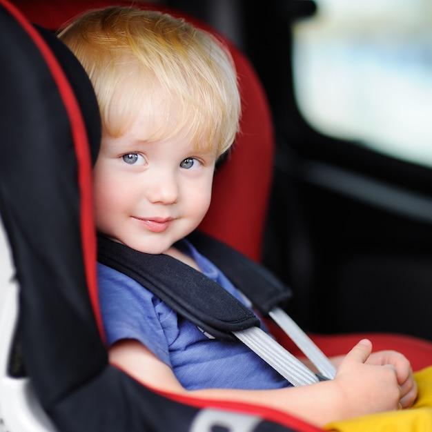 Porträt des hübschen kleinkindjungen sitzend im autositz
