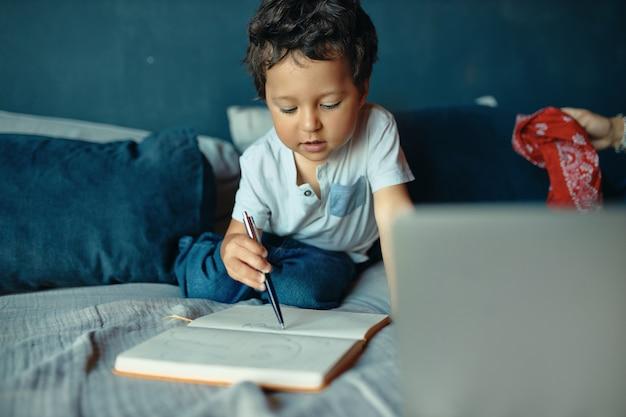 Porträt des hübschen konzentrierten kleinen jungen der gemischten rasse, der mit skizzenbuch und bleistift auf bett sitzt, zeichnung, fokussierten gesichtsausdruck habend